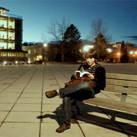 a student reading a book outside the library