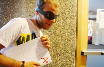 a suspicious person with a mask stealing A+ paper