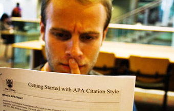 a student reading instruction on citation with a concentrated face