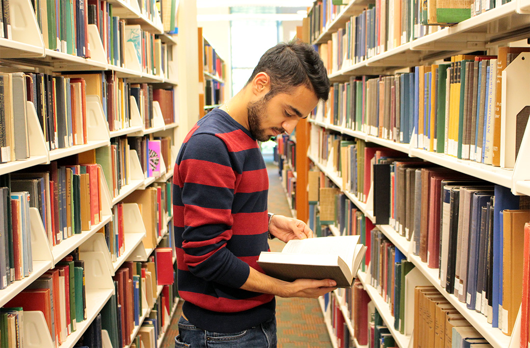 a student looking for books at a library