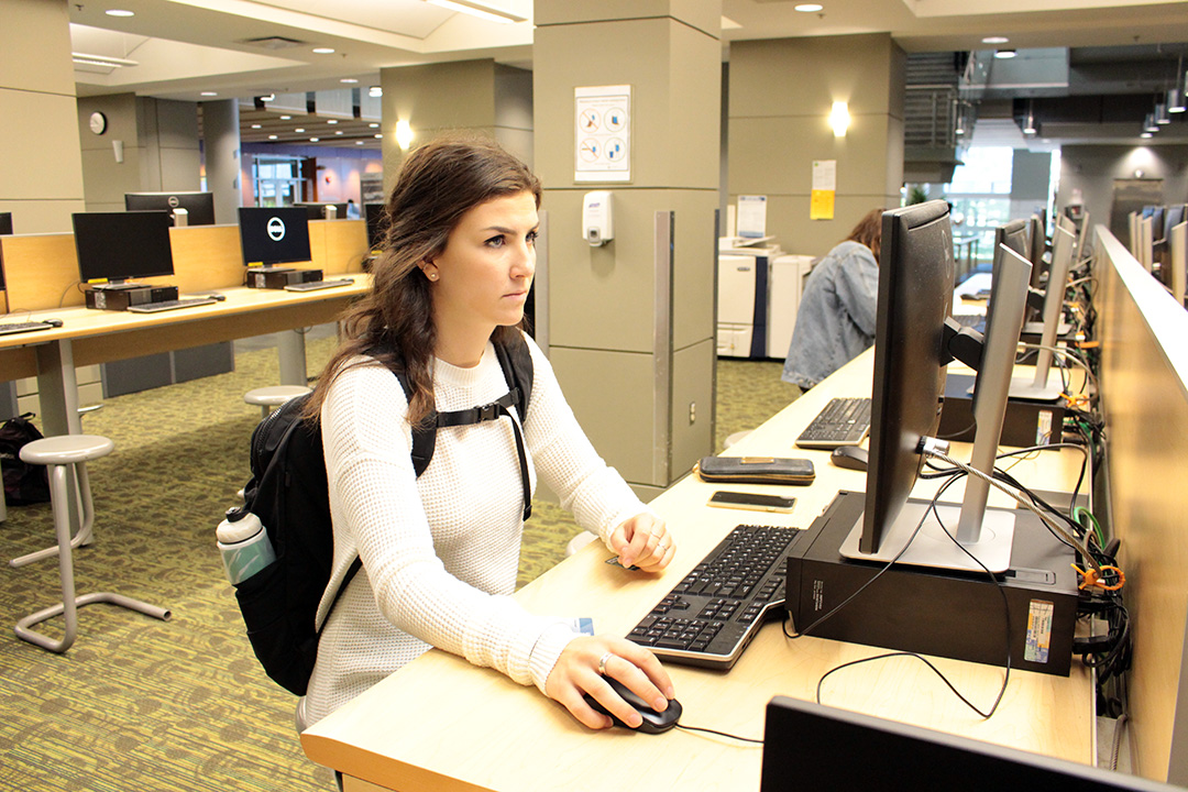 a student at a computer station inside the library